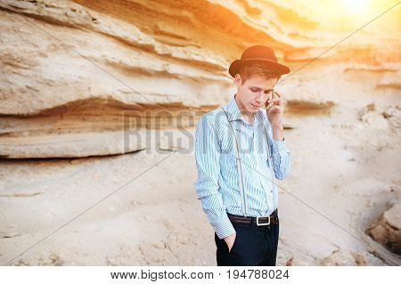 Attractive Man Is Standing In The Middle Of A Sand Quarry And Making A Call From A Smartphone
