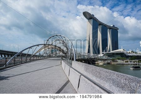 Singapore - June 17 2014 : Concrete covered with stainless bridge to Marina Bay Sands Hotel in a cloudy day in Singapore