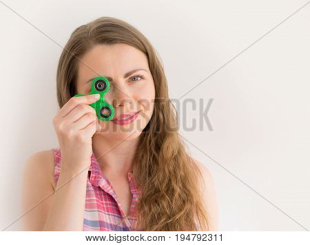 Girl playing with a colourful hand fidget spinner toy.