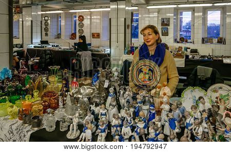 Moscow, Russia - March 19, 2017: Counter with vintage ceramic dishes and porcelain figurines on the flea market. Selective focus on a colorful plate. Saleswoman on the background.