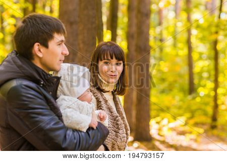 Happy young family in the autumn park outdoors on a sunny day. Mother, father and their little baby boy are walking in the park. Love and family concept
