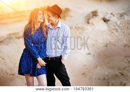 An Attractive Man Hugs A Beautiful Woman In A Blue Dress In The Middle Of A Sandy Canyon. Lovers Are