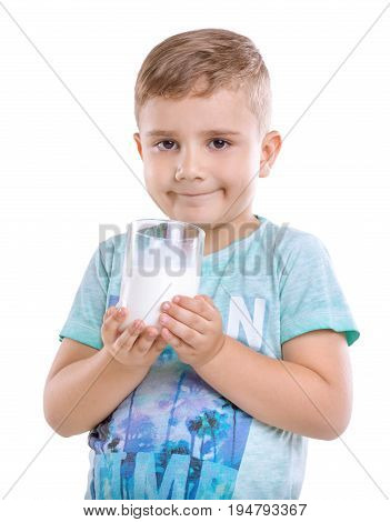 Amazing and cute little boy with blonde hair and in blue t-shirt holds a glass full of organic milk in two hands, isolated on white background.  Charming baby boy with healthy, organic and fresh milk.