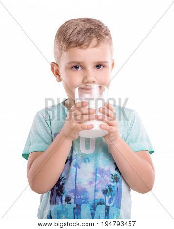 Close-up portrait of a little cheerful child with dimples on his cheeks holding a glass of fresh milk.  A smiling boy is wearing a blue T-shirt with patterns and holds a large glass of milk.