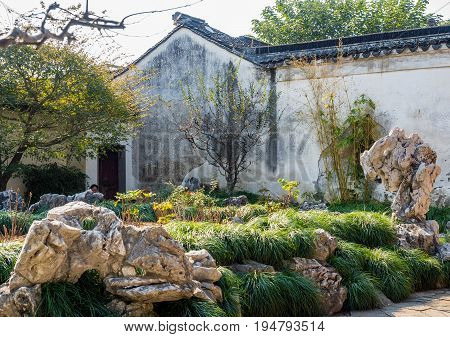 Suzhou, China - Nov 5, 2016: Master of Nets Garden (Wang Shi Yuan) - A tranquil traditional Chinese garden scene, featuring landscaped trees, rockery, and bush.