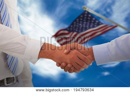 Close-up shot of a handshake in office against blue sky with clouds