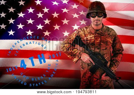 Portrait of soldier holding rifle against close-up of american flag