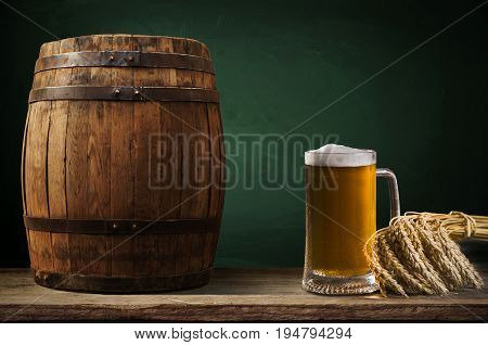Beer barrel with beer glass on table on wooden background.