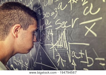 tired student and classic blackboard with math sign