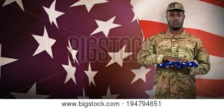 Portrait of soldier holding American flag against focus on usa flag