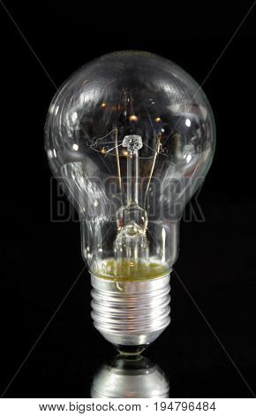 Classic electric bulb on black background. Old lightbulb.