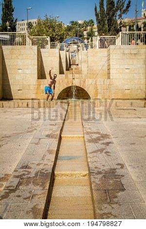 JERUSALEM ISRAEL - OCTOBER 3: Water flowing down the stone steps. Man posing to the camera Cascade fountainin Teddy Park in Jerusalem Israel on October 3 2016