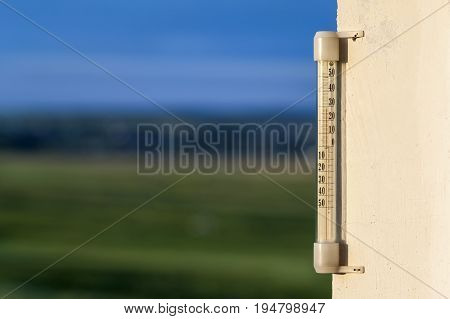 Thermometer celsius showing warm temperature on blurred green background. Weather forecast concept.