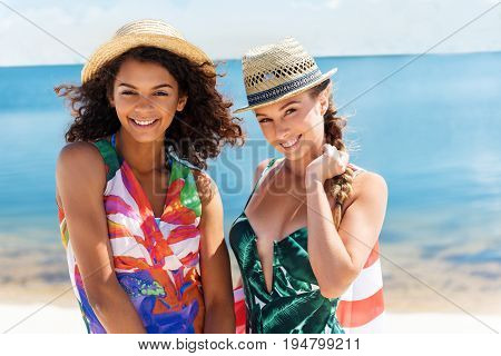 Waist up portrait of two young happy girls with toothy smiles and in straw hats standing on river shore. One girl is holding piece of cloth by one hand on her back