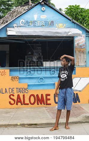 LAS TERRENAS, DOMINICAN REPUBLIC - SEPTEMBER 28, 2016: unidentified teen boy standing in front of cafeteria in the village. In the Dominican Republic child labour remains a very real problem.