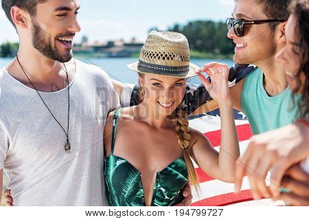 Waist up portrait of happy young woman in straw hat standing in hugs of two youthful cheery men and one mulatto girl. They are laughing and looking at each other