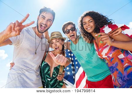 Waist up portrait of group of joyful young men and girls resting on summer beach. They are standing in pairs and hugging each other. Low angle