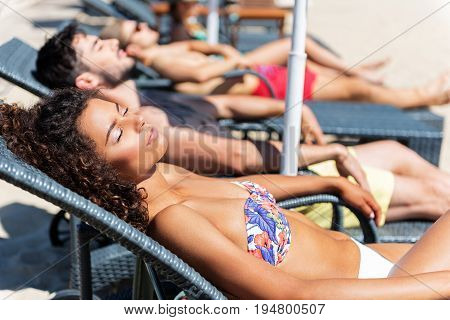 Happy young mulatto girl in bikini is lying on sunbed with two men beside her. She is having sunbathes with her eyes closed