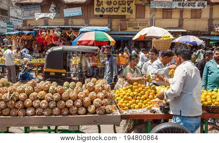 MYSORE, INDIA - FEB 16, 2017: Crowd of people near Pineapple and orange marketplace at busy street farmers market on February 16, 2017. Mysore of Karnataka has a population of 900000