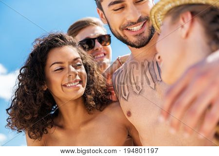 Low angle of young happy boys and girls standing close to each other in friendship hugs. Everybody is looking with toothy smiles at girl in straw hat