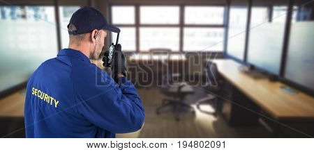 Rear view of focused security officer talking on walkie talkie against table and empty chairs in office