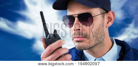 Close up of security officer talking on walkie talkie  against blue sky with clouds