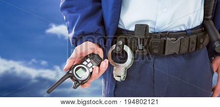 Mid section of security officer holding walkie talkie against blue sky