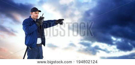 Security officer pointing away while talking on walkie talkie against cloudy sky