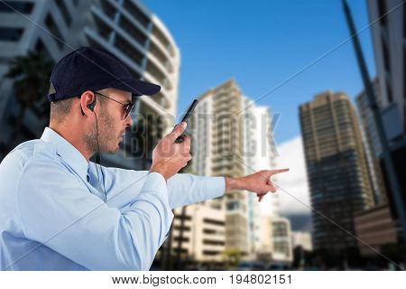 Security officer pointing away while talking on walkie talkie against buildings in city