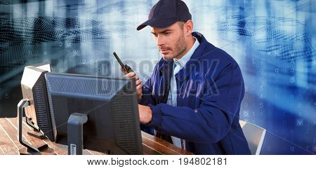 Focused security officer looking observing computer monitors and talking on walkie talkie against virus background