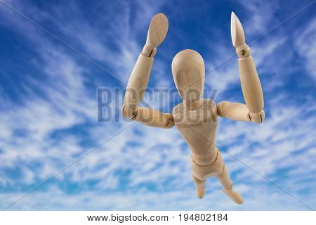 3d image of carefree wooden figurine with arms raised standing  against view of the blue sky
