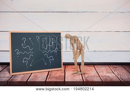 Injured 3d  wooden figurine standing with hands on knee against black board on a wooden table