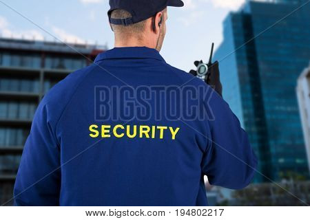 Rear view of security officer talking on walkie talkie against view of residential buildings