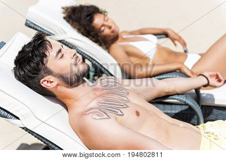 Calm youthful guy with beard and tattoo on chest is lying on beach lounger and sunbathing. He is closing his eyes. Relaxed mulatto girl in white bikini on background. Leisure concept