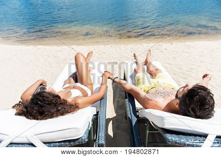 Forever together. Top view of young couple lying on sunloungers on beach close to water. They are holding by hands while taking tan