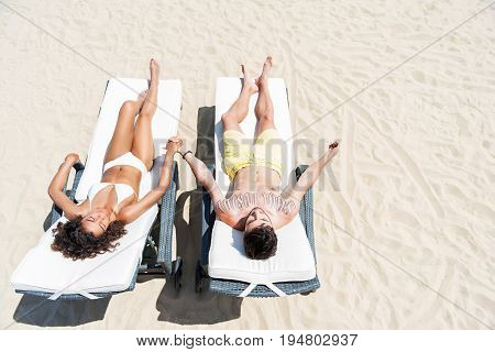 Top view of young couple lying with closed eyes on sunbeds on sand and holding arms together. They are wearing swimsuits while sunbathing