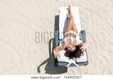 Full length portrait of young happy mulatto girl in bikini lying on sunbed on beach sand. She is waving by hands and smiling. Top view. Copy space in left side