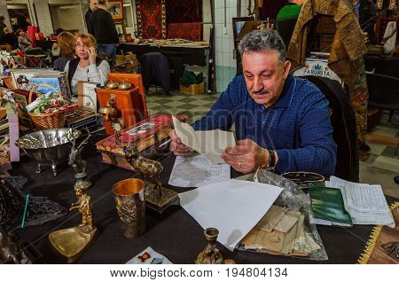 Moscow, Russia - March 19, 2017: An elderly gray-haired man in retirement age is reading document with handwritten text, sitting down at a table, surrounded by old objects. Scene on the flea market.