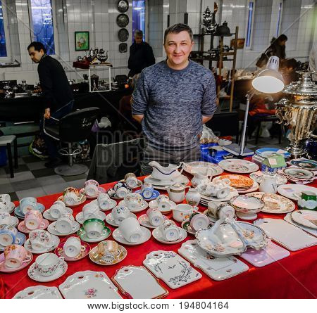 Moscow, Russia - March 19, 2017: Counter with antique porcelain and earthenware 19th century on the flea market. Selective focus on the dishes, the seller in the background.
