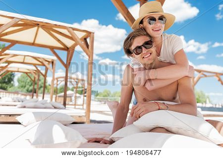 Waist up portrait of cheery young couple in sunglasses sitting on comfortable sunbed with fabric roof, mattresses and pillows. Girl in sunhat is hugging her friend from back. Copy space in left side