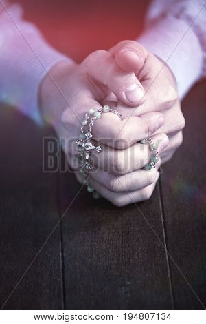 Praying hands of man with rosary on wooden desk