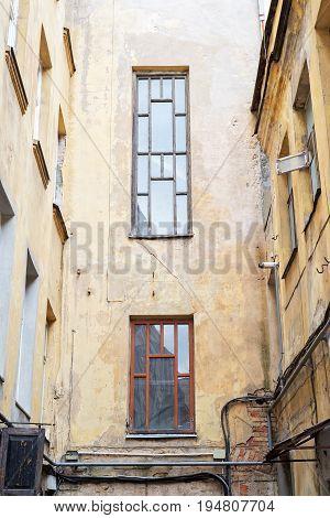 Yard among old grunge houses with big windows