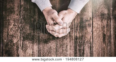 Cropped hands of man praying on wooden desk