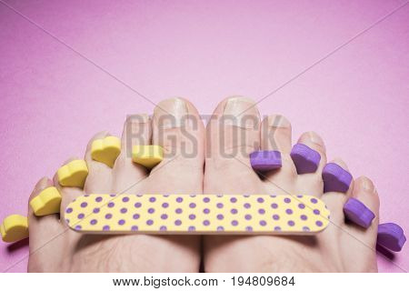 Male pedicure, nail file on a mauve background