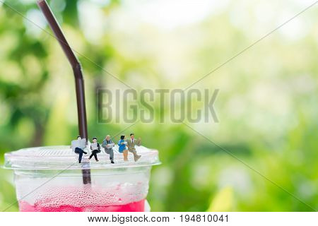 Miniature businessman and businessgirl are reading a book and sitting on the plastic cup of drink using as a business and education concept.