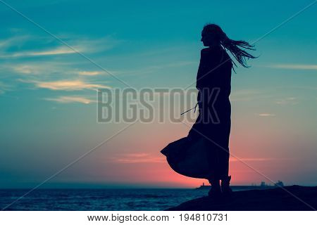 Silhouette of woman in long dress standing on the seashore after sundown.