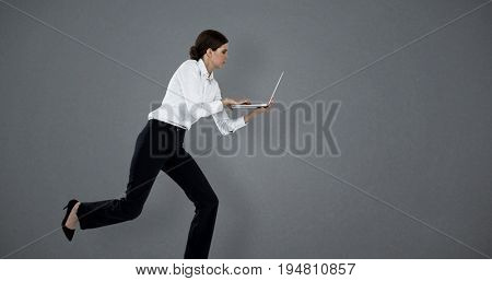 Full length of businesswoman running while using laptop against grey background