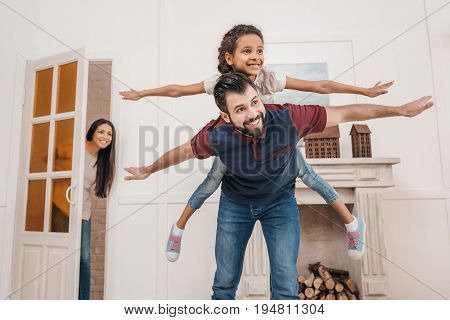 Happy father piggybacking cute little daughter at home