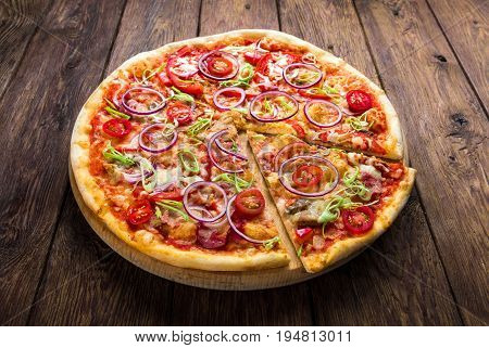 Pizza on wood background, with onions, bacon and cherry tomatoes, thin pastry crust, closeup