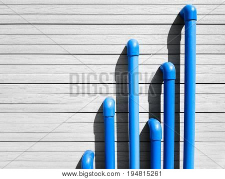 Blue PVC pipes emerge from a gray wooden wall with horizontal lines